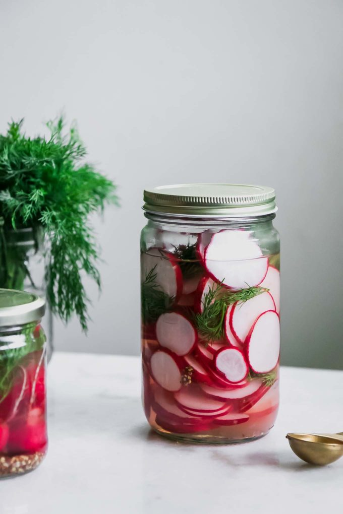 a jar of sliced pickled radishes on a white table with fresh dill
