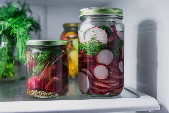 two jars of whole and sliced pickled radishes in a the refrigerator