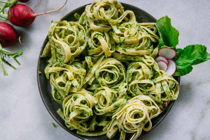 pesto pasta on a blue plate with sliced radishes