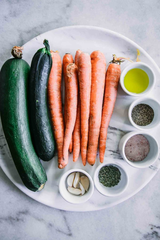zucchini, carrots and small bowls of oil and spices on a white marble countertop