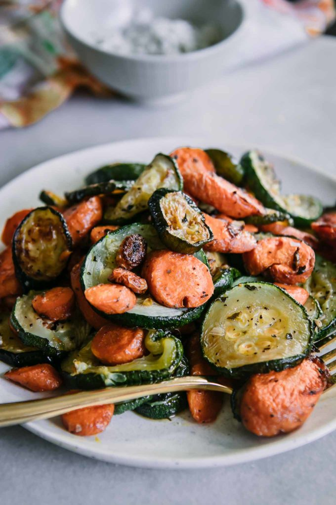 close up photo of roasted carrots and zucchini on a white plate