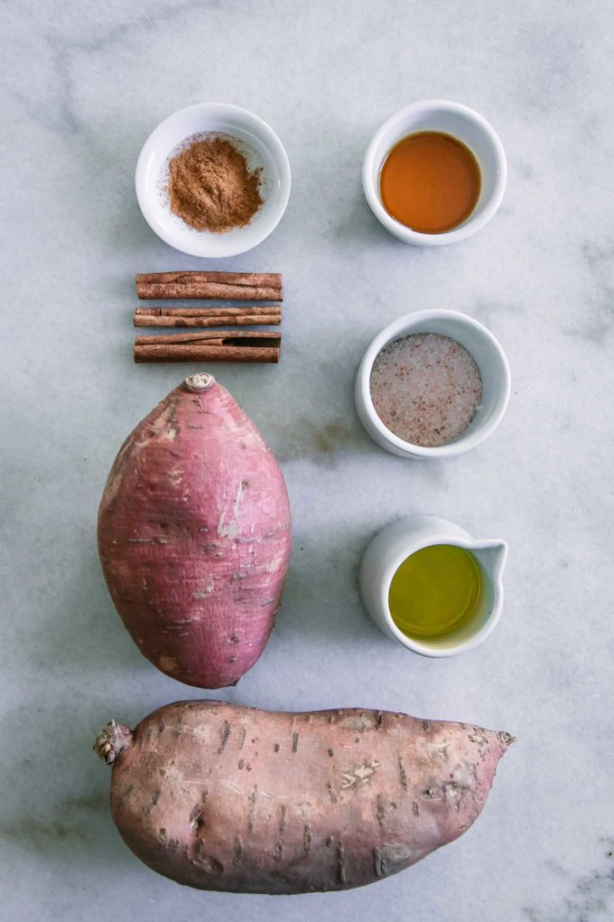 sweet potatoes, olive oil, salt, maple syrup, and cinnamon on a white table