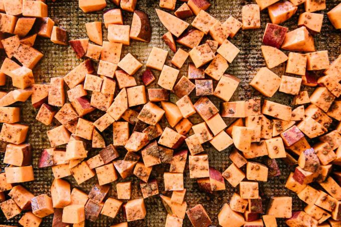 cut sweet potatoes on a baking sheet with cinnamon and maple syrup