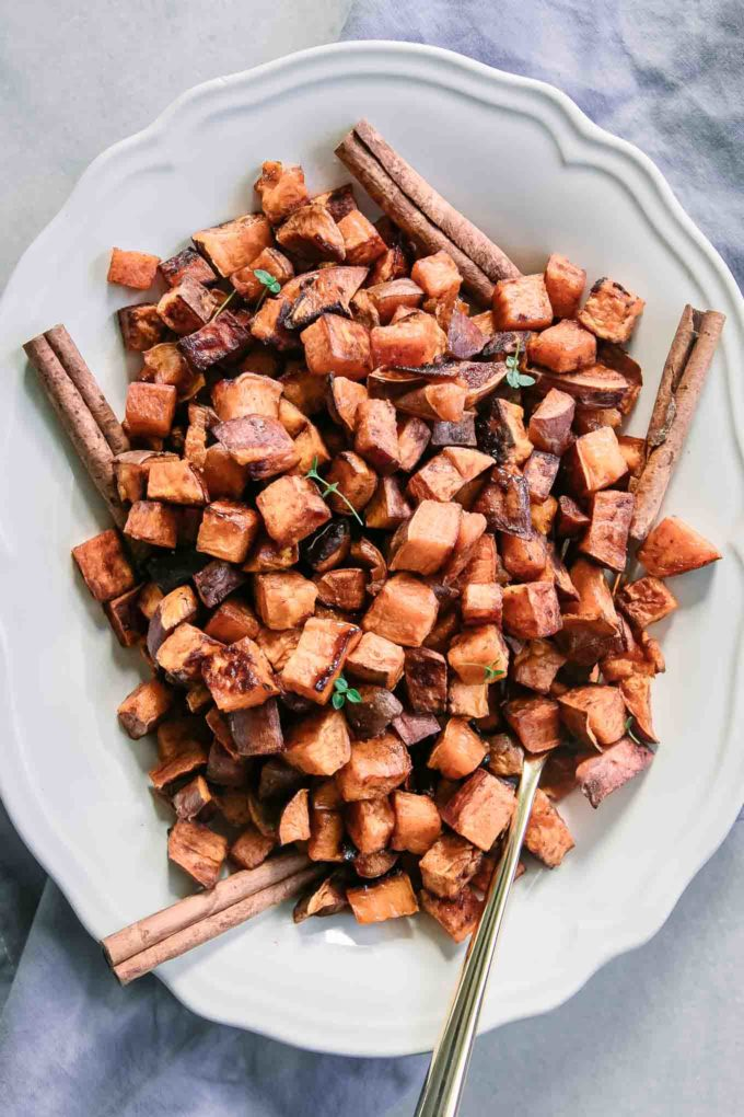 roasted sweet potatoes and cinnamon sticks on a white plate with a gold fork