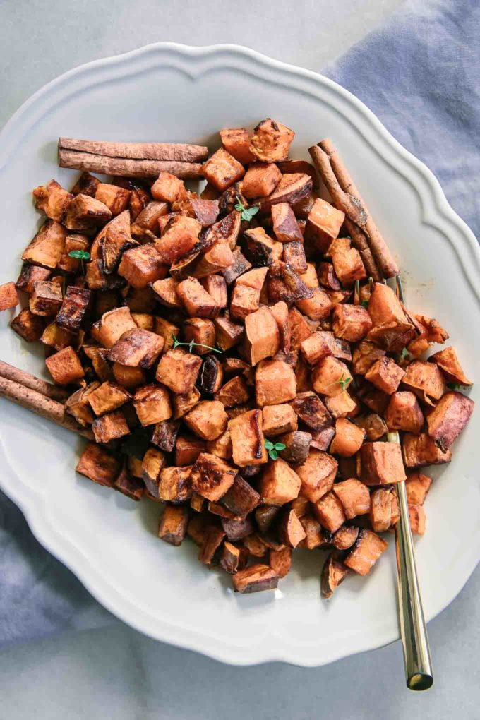 baked sweet potatoes on a white plate with cinnamon sticks