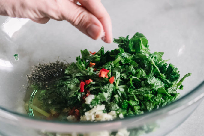 a hand sprinkling salt over chimichurri ingredients in a glass mixing bowl