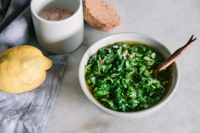 a bowl of chimichurri with a wooden spoon on a white table with radishes and lemons