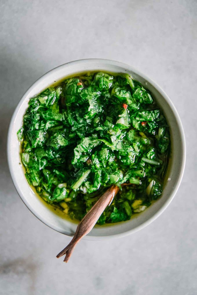 a bowl of green chimichurri on a white table