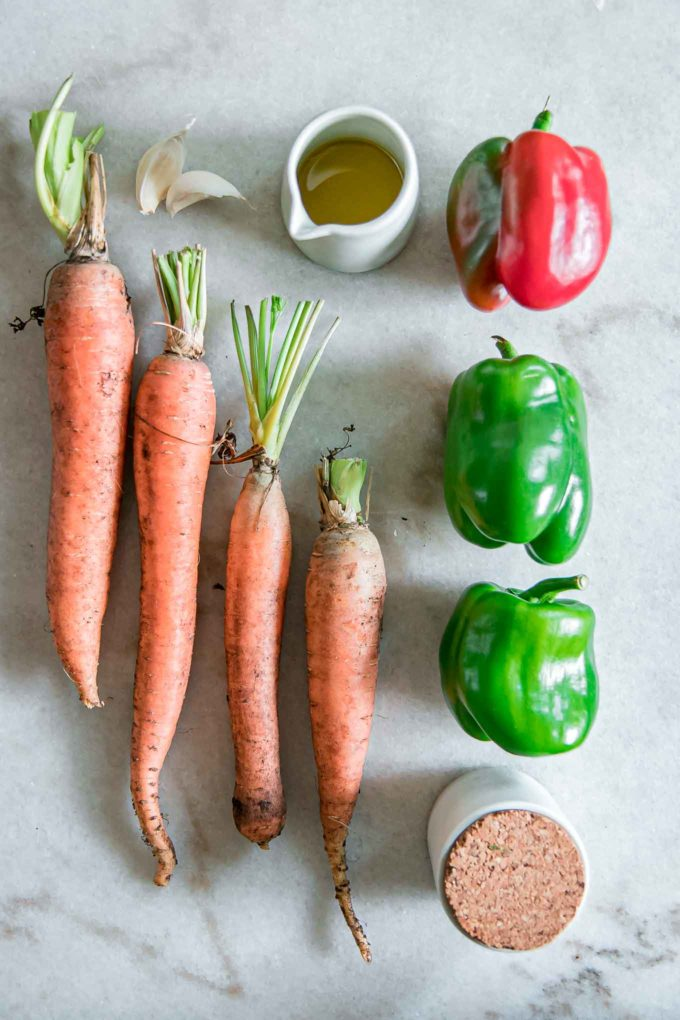 four carrots, three bell peppers, olive oil, and salt on a white table