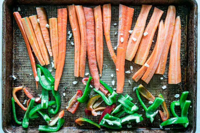 sliced carrots and bell peppers on a sheet pan