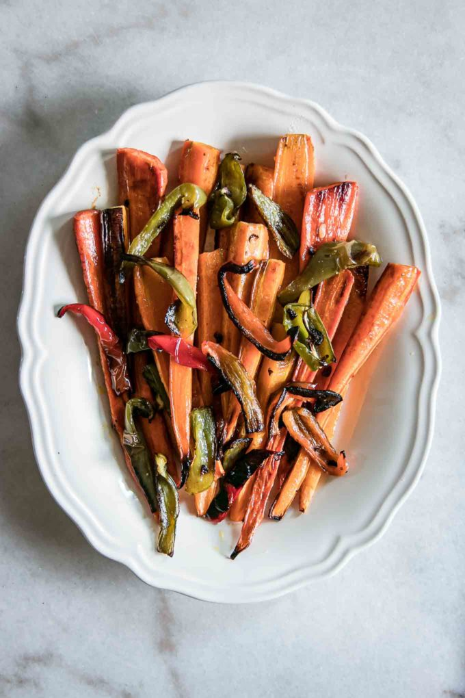 oven roasted long carrots and sliced bell peppers on a serving plate
