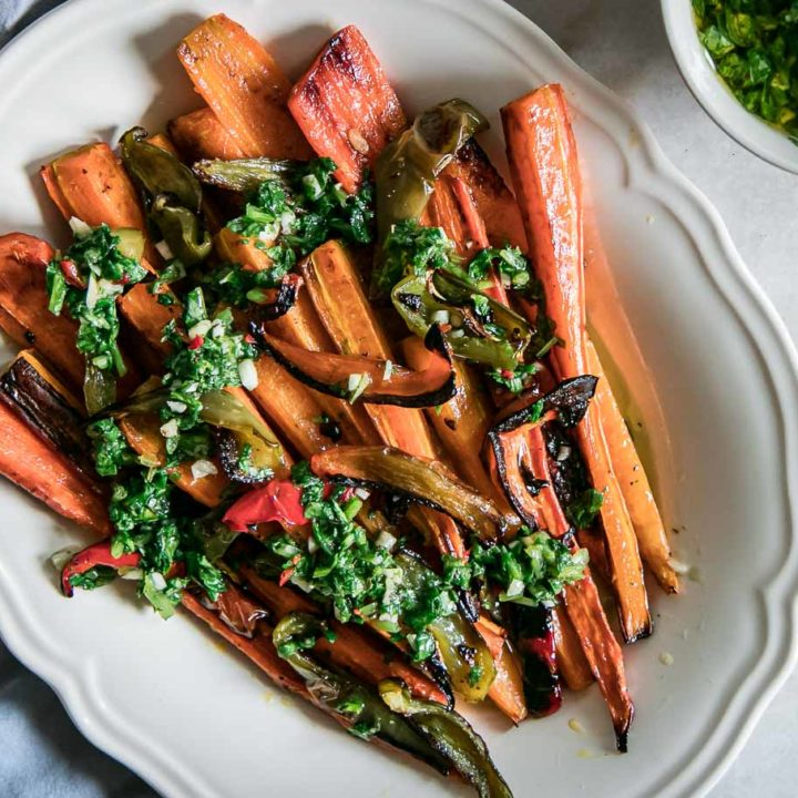 long roasted carrots and sliced bell peppers on a white plate