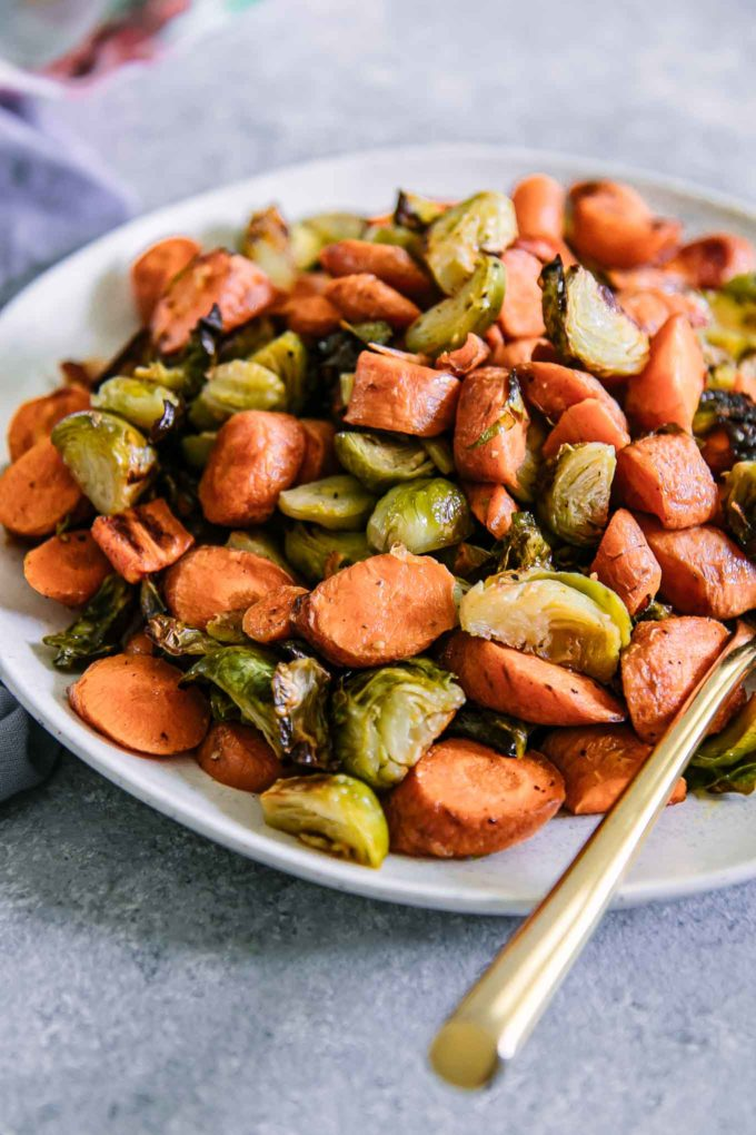 a plate of baked carrots and brussels sprouts