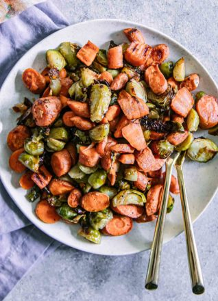roasted brussels sprouts and carrots on a white plate with a gold fork