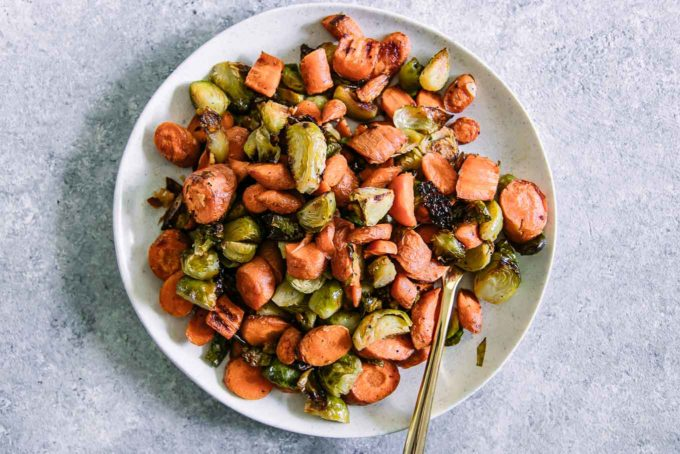 roasted carrots and brussels sprouts on a white p