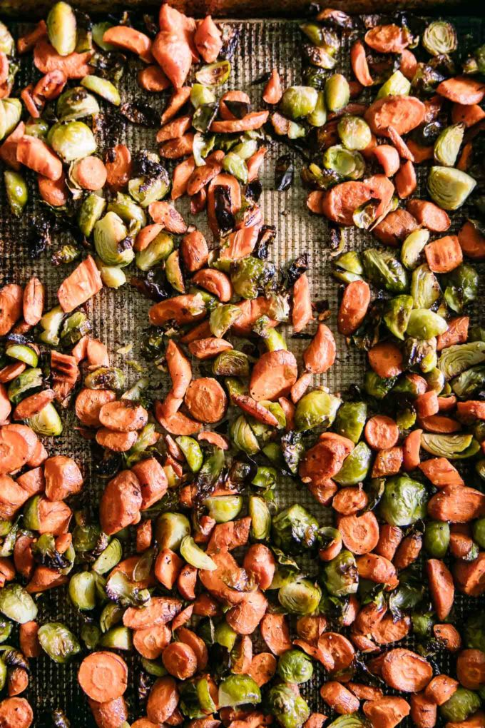 roasted carrots and brussels sprouts on a roasting pan