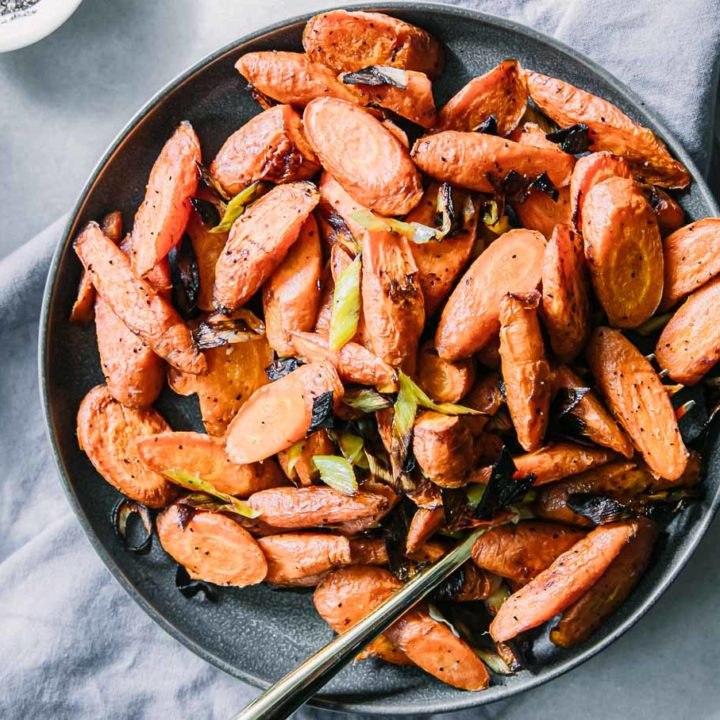 baked carrots and leeks on a blue plate on a white table with a gold fork