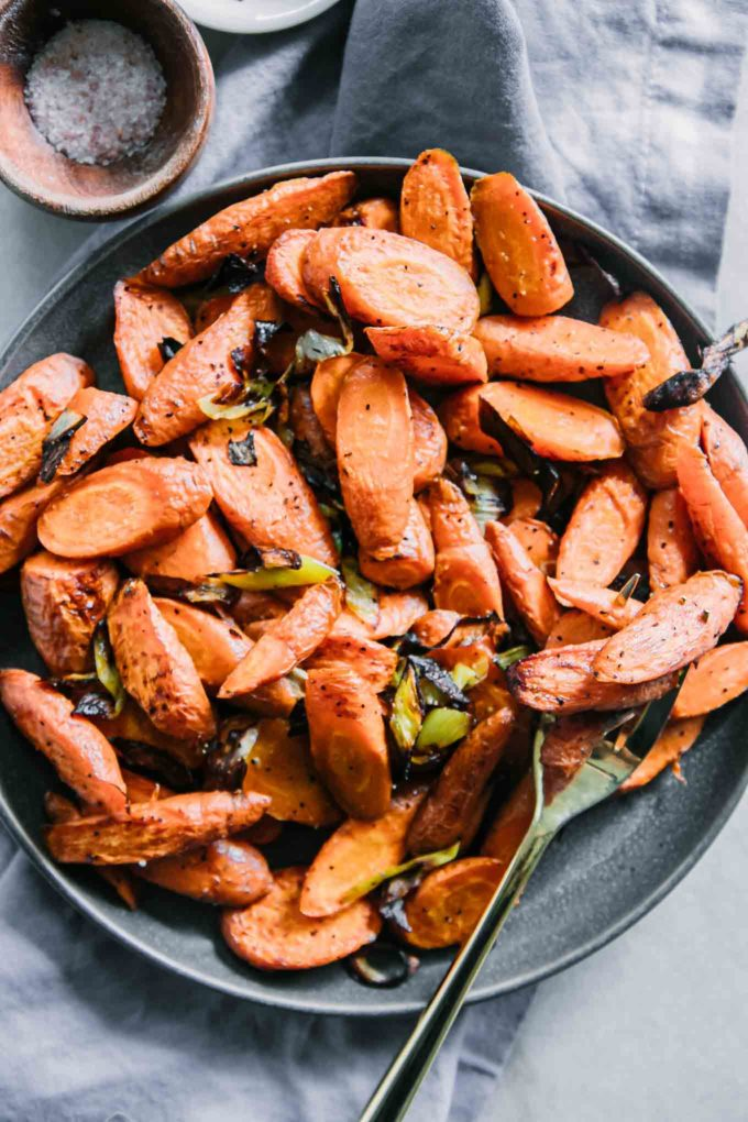 roasted carrots and leeks on a blue plate with a gold fork