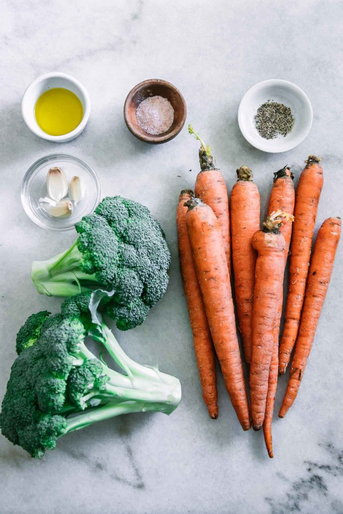 carrots, a head of broccoli, and bowls of garlic, olive oil, salt, and pepper on a marble countertop