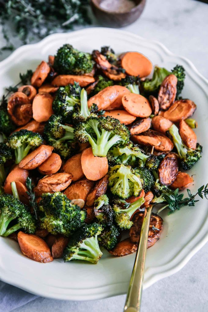 oven roasted carrots and broccoli on a white plate with a gold fork