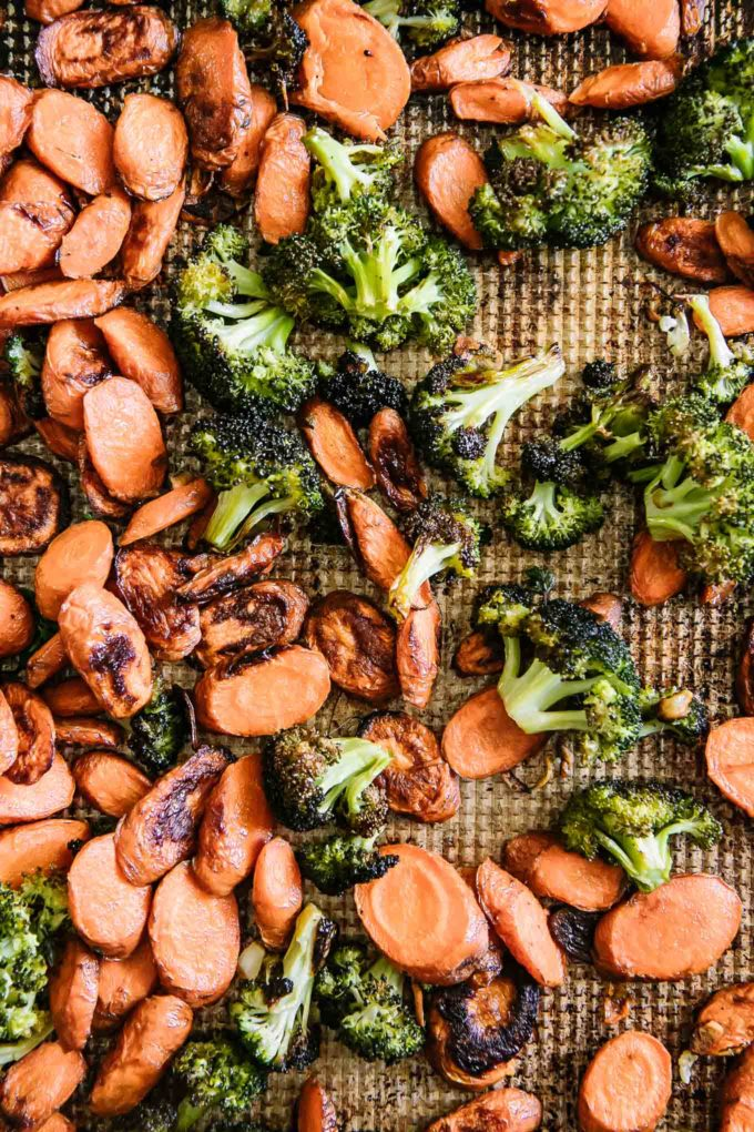 cooked carrots and broccoli on a sheet pan after roasting