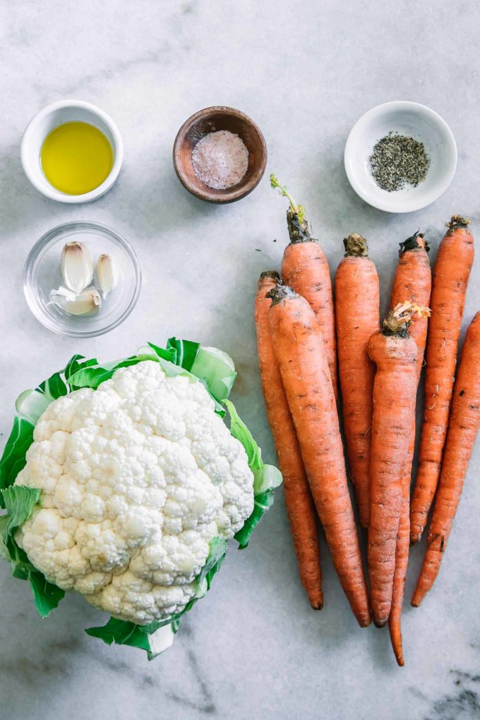carrots, a head of cauliflower, and bowls of oil, garlic, salt, and pepper