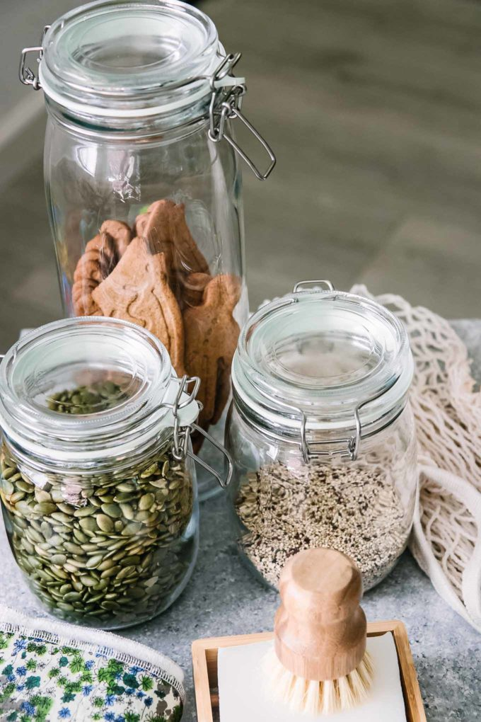 glass food storage containers filled with dried foods on a blue table