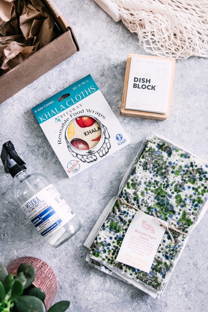 a glass spray bottle, reusable paper towels, bar dish washing soap, and beeswax wrap on a blue table