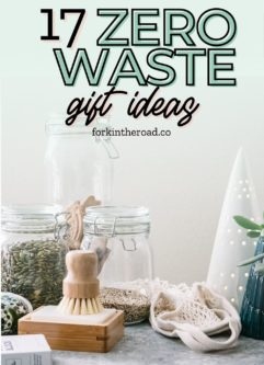 a reusable dish brush, glass food storage jars, and a reusable shopping bag on a table with holiday tree decorations