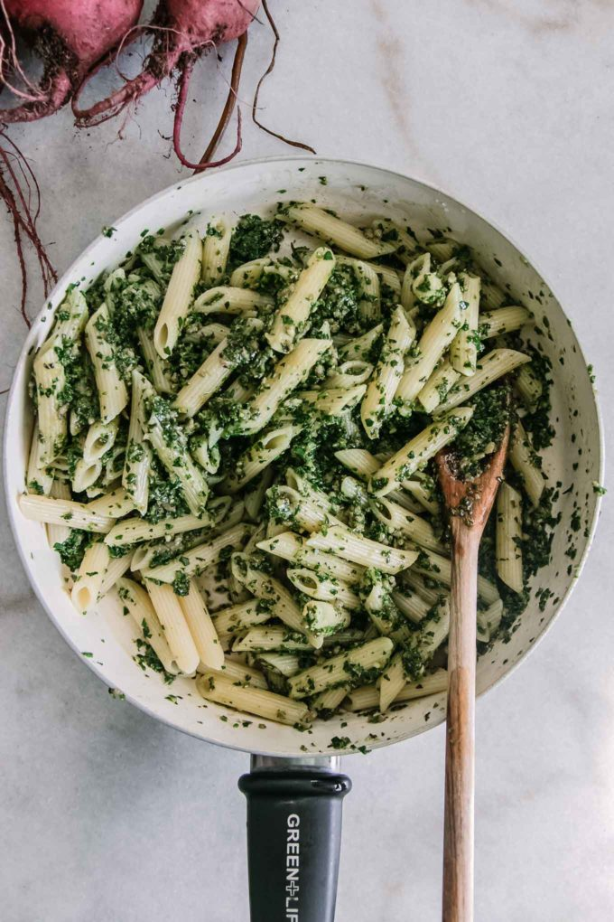 penne noodles in a pan with pesto and wooden spoon on a white table