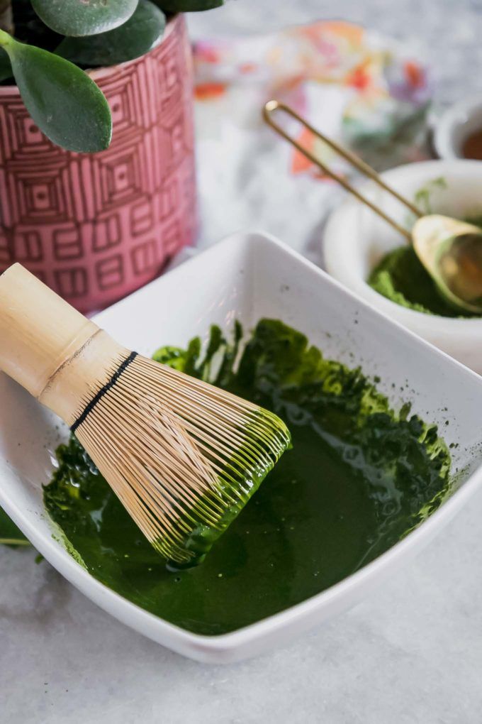 a bowl with matcha green tea powder dissolved in water and a wooden matcha whisk