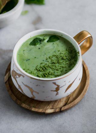 a green tea matcha latte in a white ceramic mug on a wooden saucer