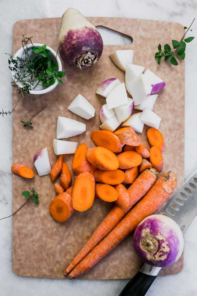 sliced carrots, turnips, fresh herbs, and a knife on a cutting board