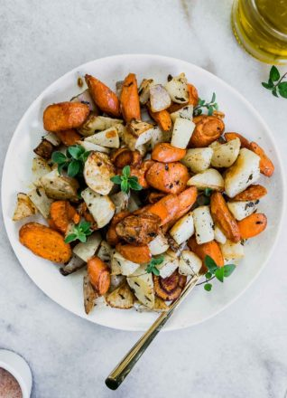 roasted turnips and carrots on a white plate with a gold fork
