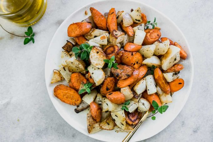 a side dish of carrots and turnips on a table with condiments