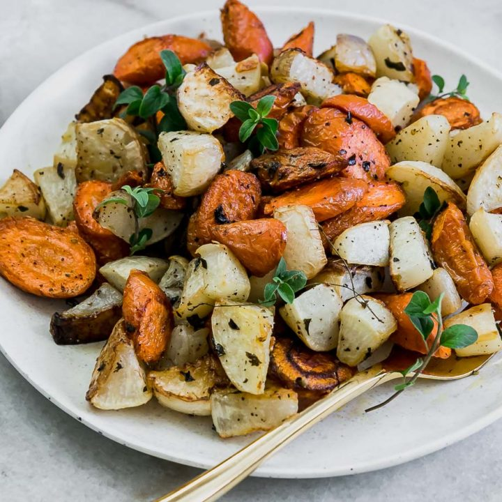 roasted carrots and turnips on a white plate on a white table