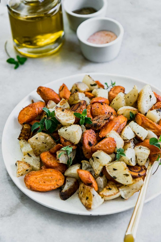 roasted turnips and carrots on a white plate on a white table with a bottle of oil and bowls of salt and pepper in the background
