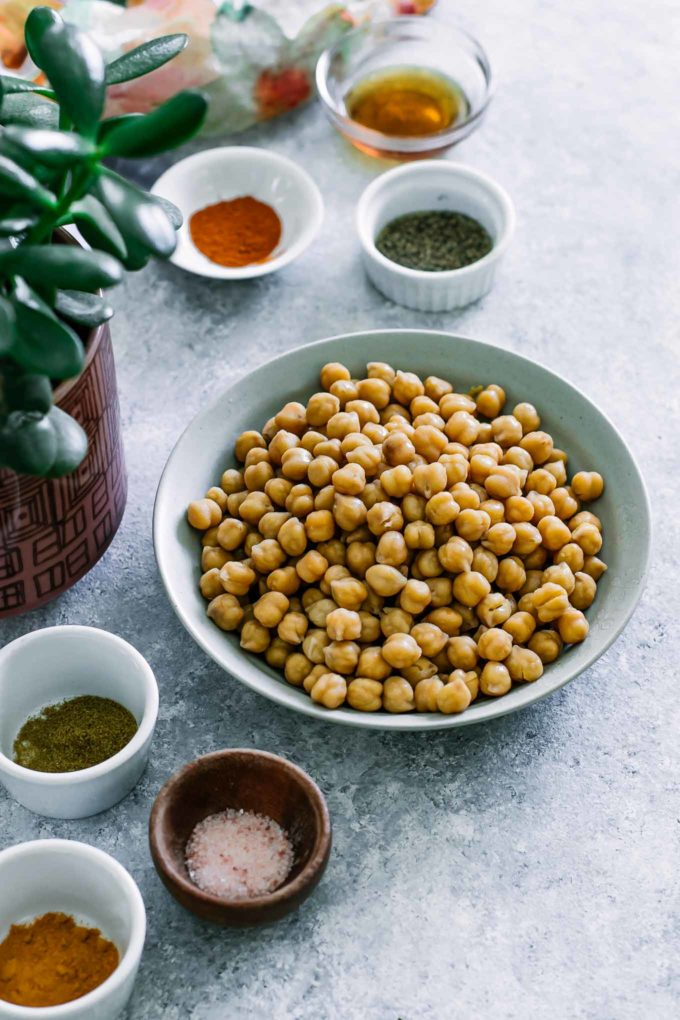 bowls of chickpeas, maple syrup, salt, and other spices on a blue table with a green plant
