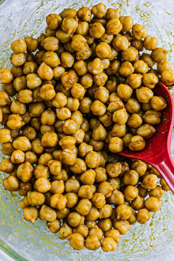 spiced chickpeas in a mixing bowl with a red spoon