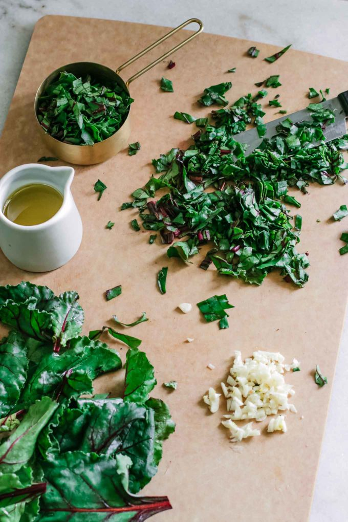 a wooden cutting board with chopped beet leaves, garlic, and a bowl of olive oil