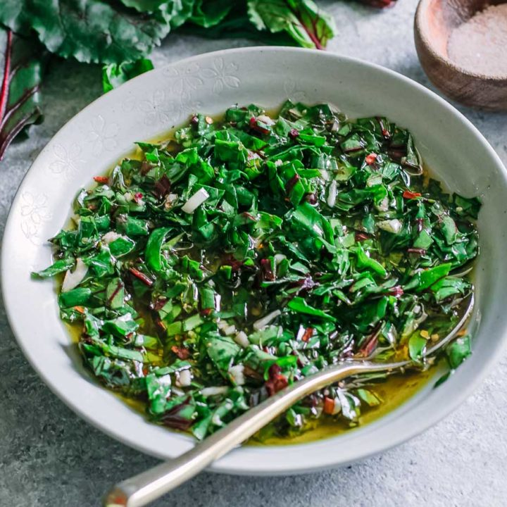 a bowl of chimichurri on a blue table