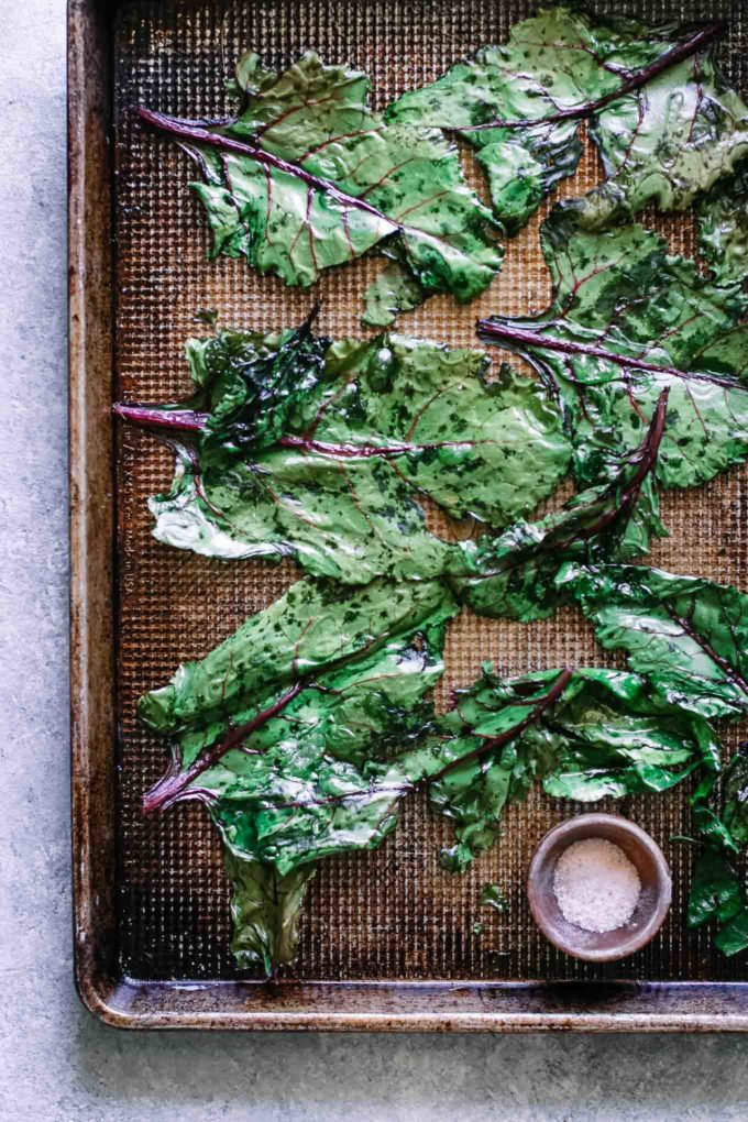 roasted beet greens on a baking sheet with a bowl of salt