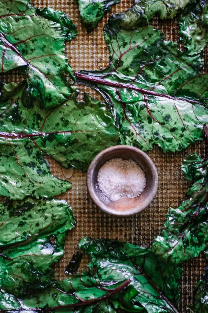baked beet leaves on a sheet pan with a bowl of salt