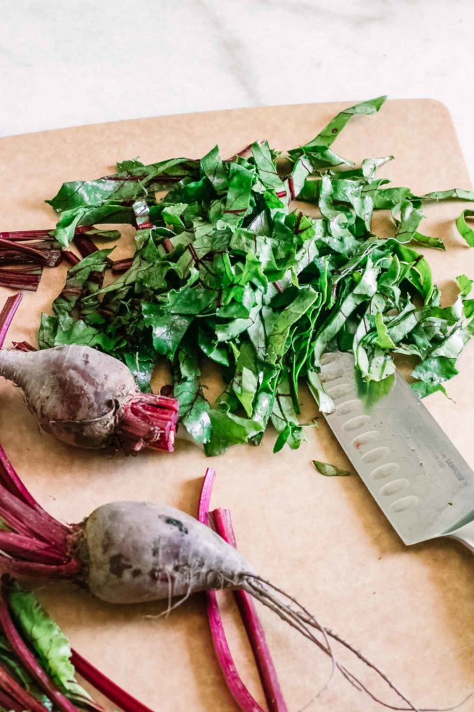 chopped beet greens and red beet roots on a brown cutting board