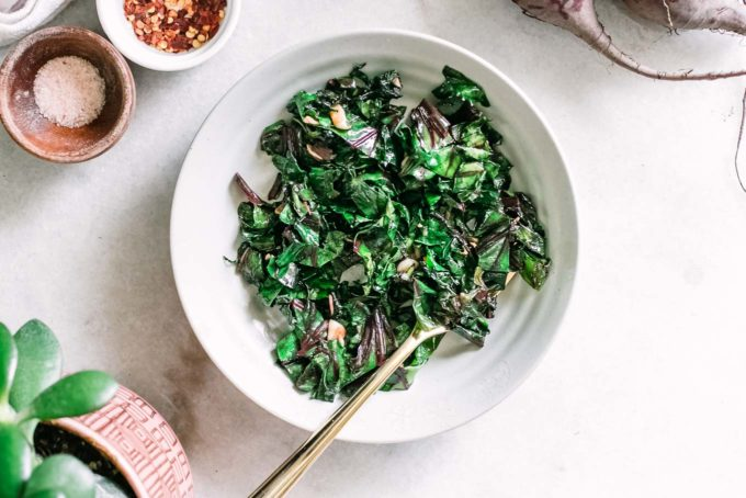 beet greens in a white bowl with a gold fork