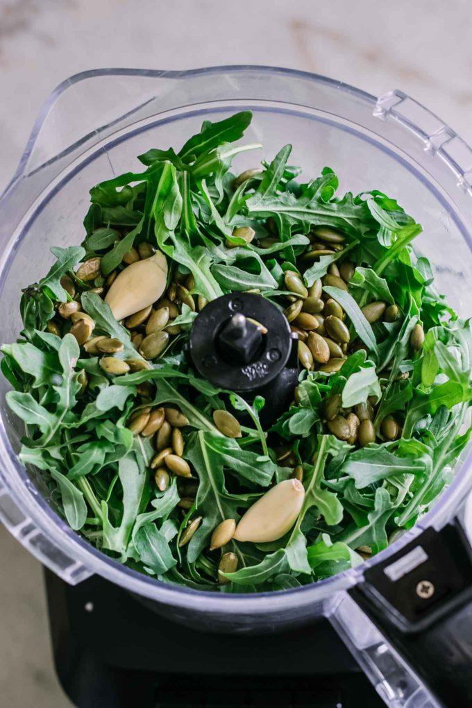 arugula, pumpkin seeds, and garlic inside a food processor