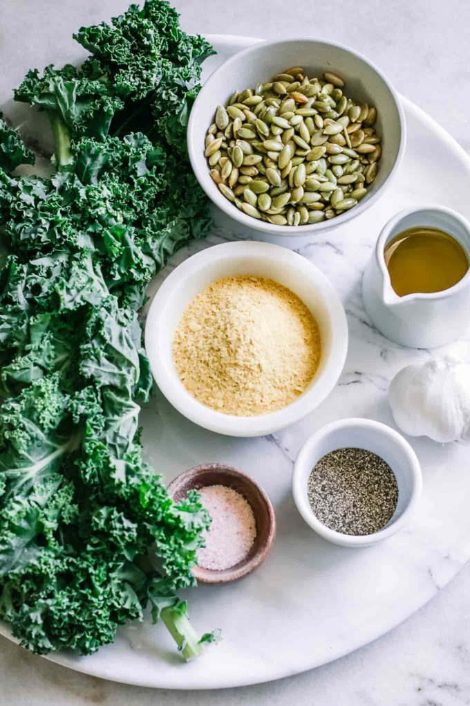 a bunch of kale and bowls of nuts, nutritional yeast, olive oil, garlic, salt, and pepper
