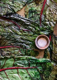 roasted chard chips on a sheet pan with a bowl of salt