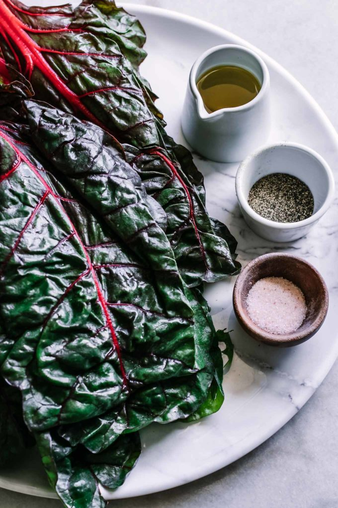 chard leaves and bowls of olive oil, salt, and pepper on a white table