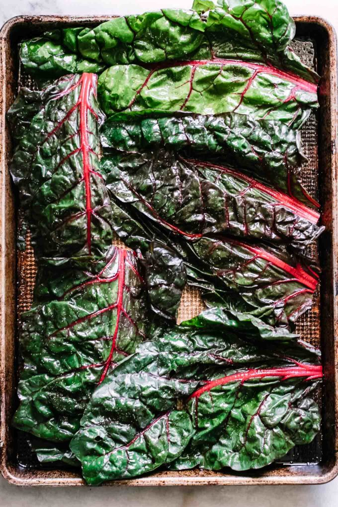 chard leaves on a sheet pan before baking